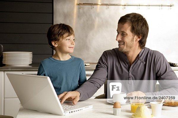 Mid Erwachsenen Mann mit einem Laptop und Blick auf seinen Sohn