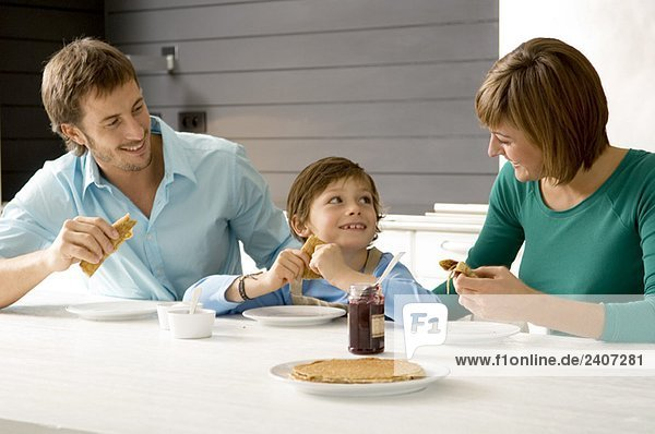 Ein erwachsener Mann und eine junge Frau beim Frühstück mit ihrem Sohn. Ein erwachsener Mann und eine junge Frau beim Frühstück mit ihrem Sohn.