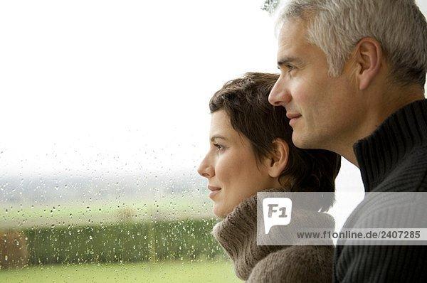 Ein reifer Mann und eine erwachsene Frau  die aus dem Fenster schaut.