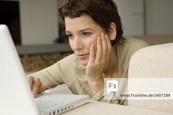 Mittlere erwachsene Frau bei der Arbeit am Laptop im Wohnzimmer