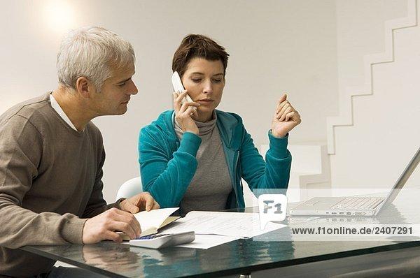 Ein reifer Mann  der Rechnungen berechnet und eine erwachsene Frau  die auf einem Handy neben ihm spricht.