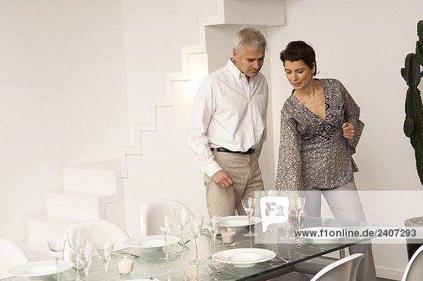 Mittlere erwachsene Frau deckt einen Esstisch und ein reifer Mann steht neben ihr.