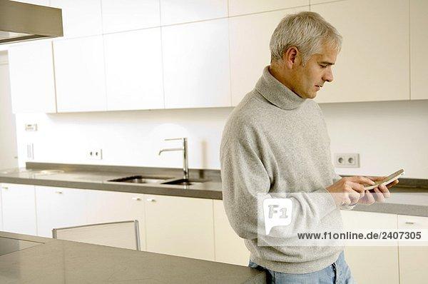 Erwachsener Mann in der Küche und SMS auf dem Handy
