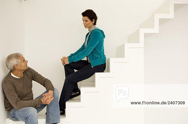 Ein reifer Mann und eine erwachsene Frau sitzen auf einer Treppe und schauen sich an.