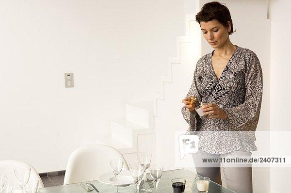 Mittlere erwachsene Frau  die eine Kerze mit einem Zigarettenanzünder an einem Esstisch anzündet.