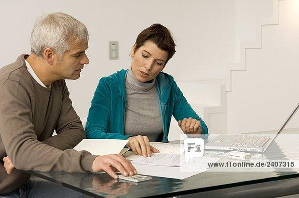 Ein reifer Mann und eine erwachsene Frau  die ihre Finanzen planen.