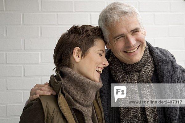 Nahaufnahme eines reifen Mannes um eine erwachsene Frau herum und lächelnd