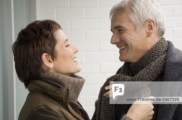 Mittlere erwachsene Frau  die den Schal eines reifen Mannes bindet.