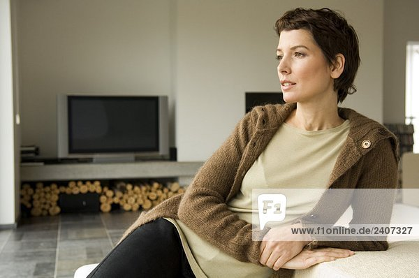 Mittlere erwachsene Frau  die sich gegen eine Couch lehnt.
