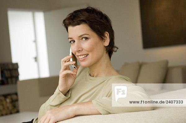 Porträt einer erwachsenen Frau  die auf einem Mobiltelefon spricht.