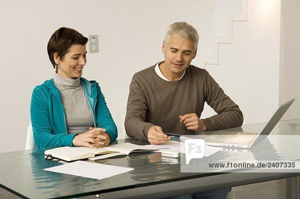 Ein reifer Mann und eine erwachsene Frau  die an einem Laptop arbeiten und eine Kreditkarte haben.