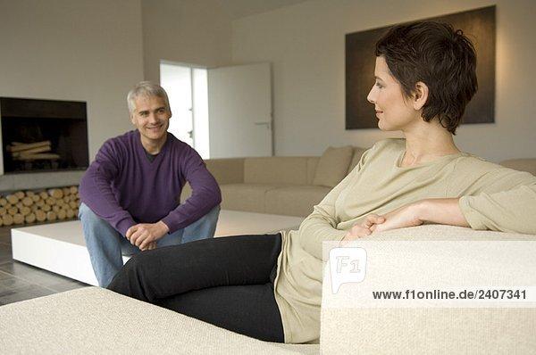 Mittlere erwachsene Frau und ein reifer Mann sitzen in einem Wohnzimmer