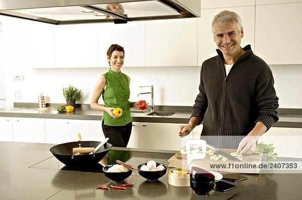 Porträt eines reifen Mannes und einer mittleren erwachsenen Frau bei der Zubereitung von Speisen in der Küche