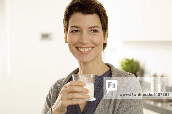 Mittlere erwachsene Frau mit einem Glas Milch Mittlere erwachsene Frau mit einem Glas Milch