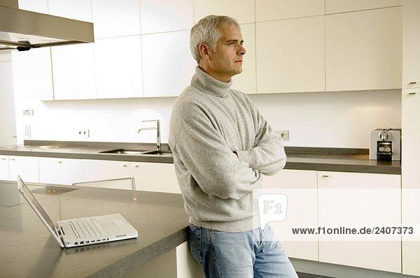 Reifer Mann  der sich gegen eine Küchenzeile lehnt.