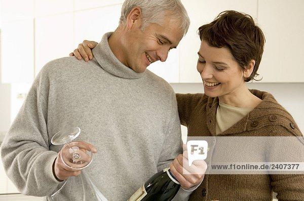 Ein reifer Mann und eine erwachsene Frau beim Anblick einer Champagnerflasche