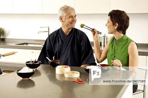 Mittlere erwachsene Frau füttert einen reifen Mann in der Küche. Mittlere erwachsene Frau füttert einen reifen Mann in der Küche.