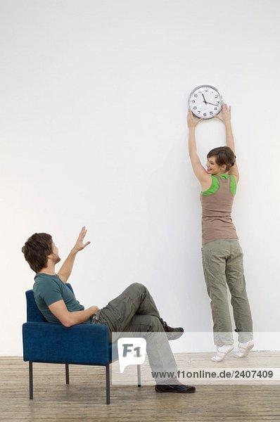 Ein erwachsener Mann  der auf seine Frau schaut  die eine Uhr an die Wand montiert.