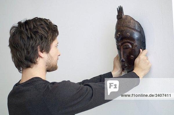 Mittlerer Erwachsener Mann  der eine Maske an einer Wand anpasst.