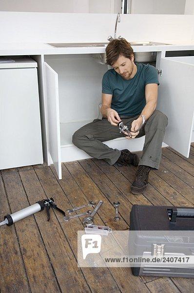 Mittlerer Erwachsener Mann  der einen Wasserhahn in der Küche repariert.