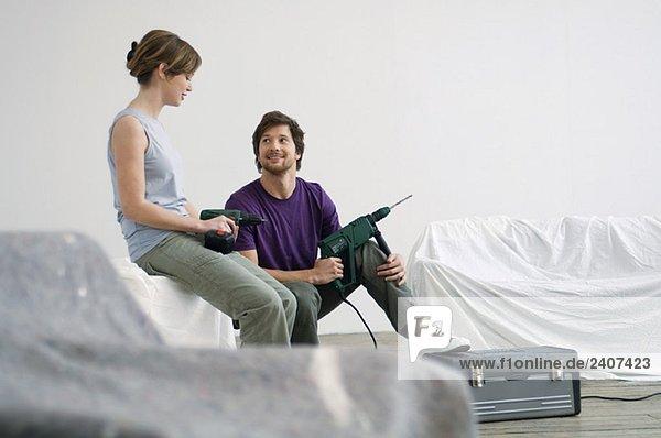 Ein junges Paar sitzt in einem Raum und hält Bohrer.
