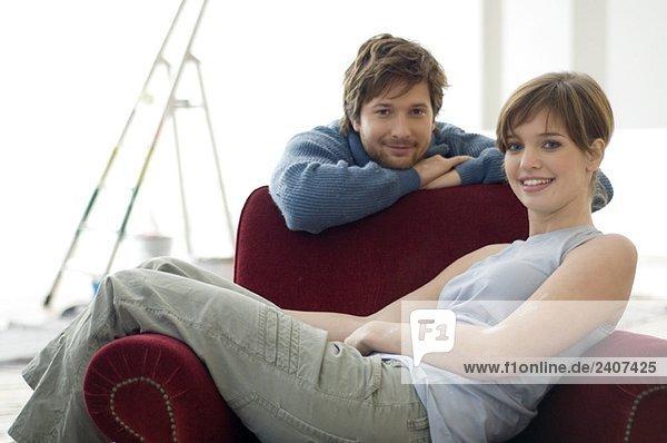 Junge Frau sitzt in einem Sessel und ein erwachsener Mann lehnt sich hinter ihr her.