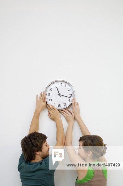 Rückansicht eines erwachsenen Mannes und einer jungen Frau  die eine Uhr an der Wand montieren.