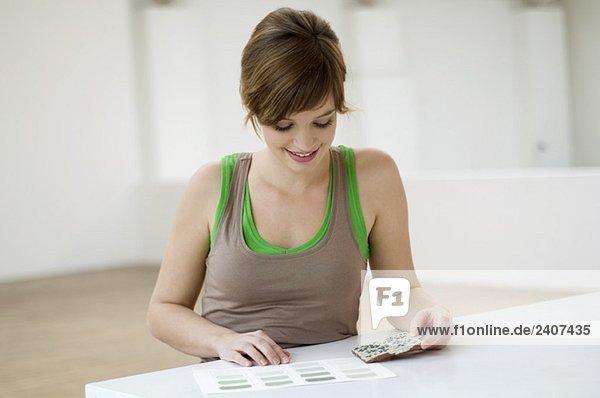Junge Frau  die eine Kachel mit einem Farbmuster auf einem Tisch kombiniert