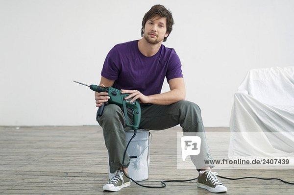 Porträt eines erwachsenen Mannes  der einen Bohrer hält und auf einer Farbdose sitzt.