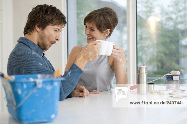 Paar haltende Tassen Tee und Lächeln