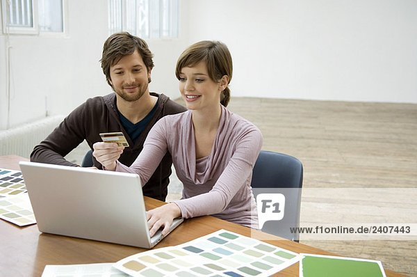 Mittlerer Erwachsener Mann und eine junge Frau  die einen Laptop benutzen und eine Kreditkarte haben.