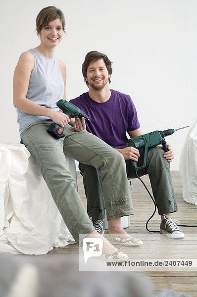Porträt eines erwachsenen Mannes und einer jungen Frau mit Bohrmaschinen