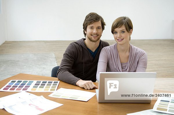 Portrait of a mid adult man and a young woman using a laptop