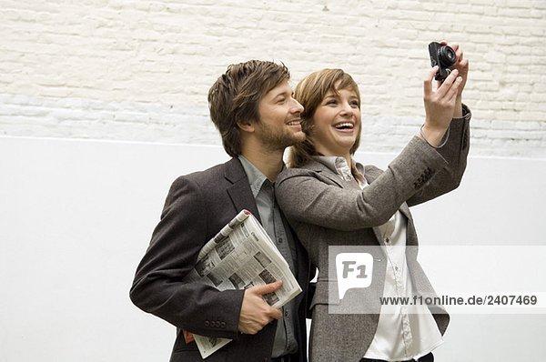 Junge Frau fotografiert mit einer Digitalkamera und einem mittleren Erwachsenen  der hinter ihr steht.