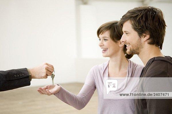 Gros plan sur main d'un agent immobilier tendant cl?©s ? un couple