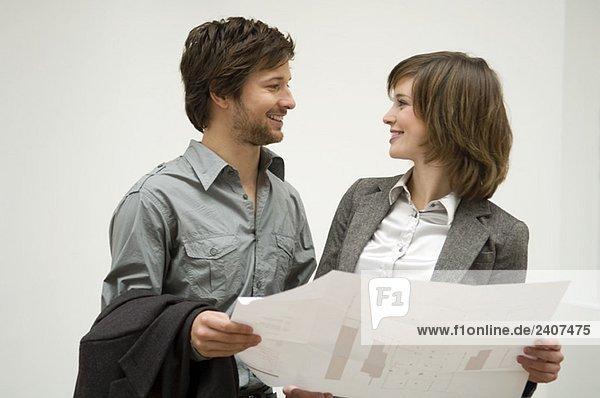 Ein erwachsener Mann und eine junge Frau  die eine Blaupause halten und sich anschauen.