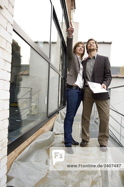 Junge Frau  die nach vorne zeigt und ein erwachsener Mann  der neben ihr steht.