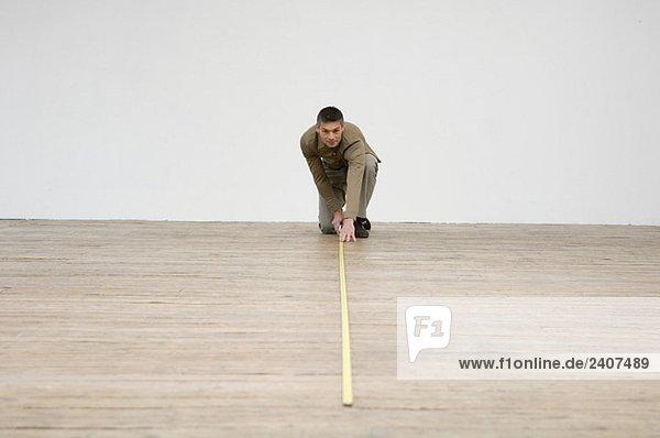 Innenarchitekt beim Vermessen des Hartholzbodens mit einem Maßband