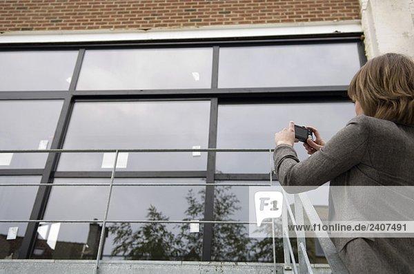 Junge Frau beim Fotografieren eines Hauses mit einer Digitalkamera