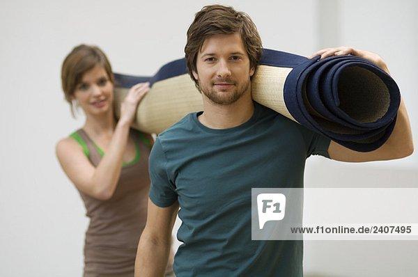 Portrait of a couple carrying a carpet