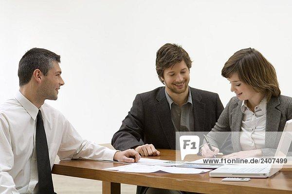 Junge Frau  die ein Dokument mit einem erwachsenen Mann und einem Immobilienmakler ausfüllt.