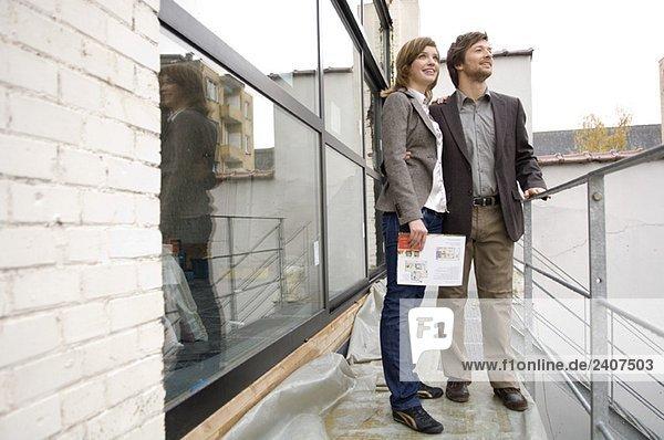 Mittlerer Erwachsener Mann und eine junge Frau  die auf einem Balkon stehen