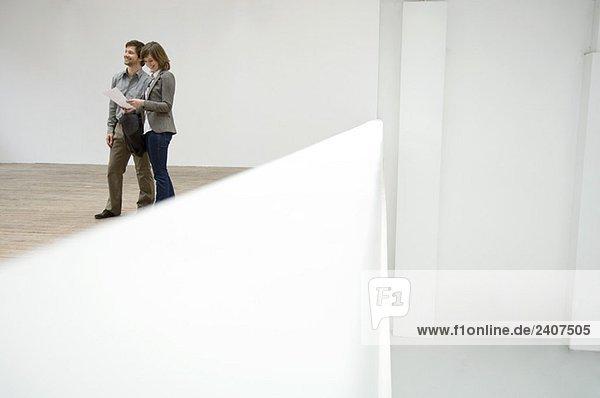 Junge Frau  die auf einen Bauplan schaut und ein erwachsener Mann  der neben ihr steht. Junge Frau, die auf einen Bauplan schaut und ein erwachsener Mann, der neben ihr steht.