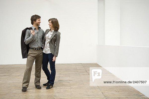 Paar steht mit den Armen umeinander in ihrem neuen Haus und lächelt.