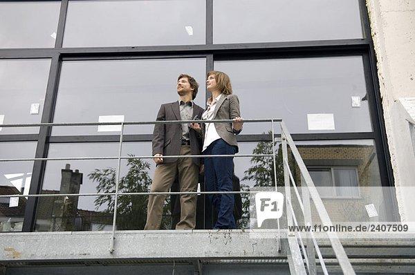 Tiefblick auf einen erwachsenen Mann und eine junge Frau auf dem Balkon