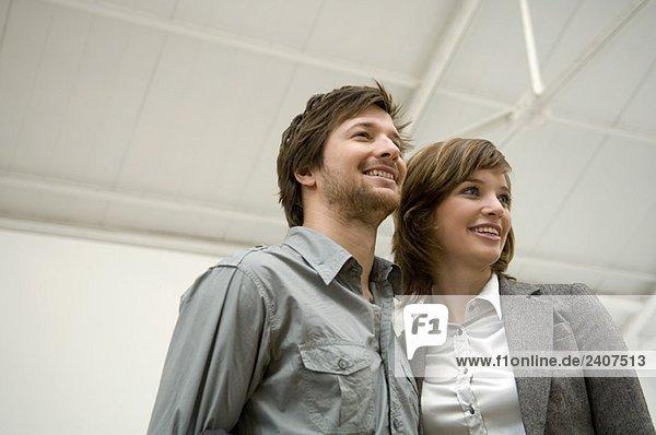 Tiefblick auf einen erwachsenen Mann und eine junge Frau  die wegschauen und lächeln.