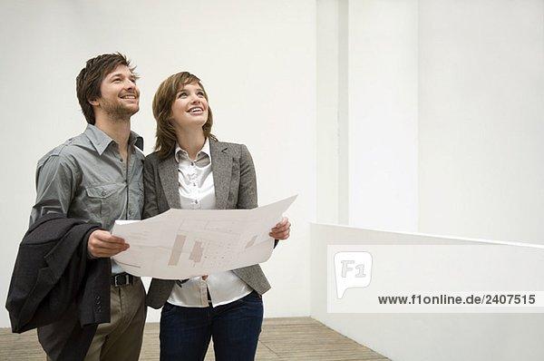 Mittlerer erwachsener Mann und eine junge Frau mit einem Bauplan