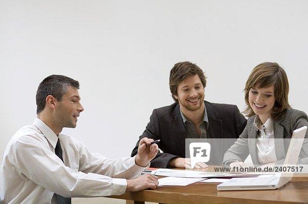 Immobilienmakler bespricht mit einem Ehepaar einen Bauplan