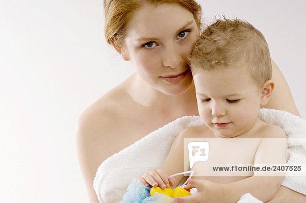 Porträt einer jungen Frau  die ihren Sohn in ein Handtuch wickelt und lächelt.