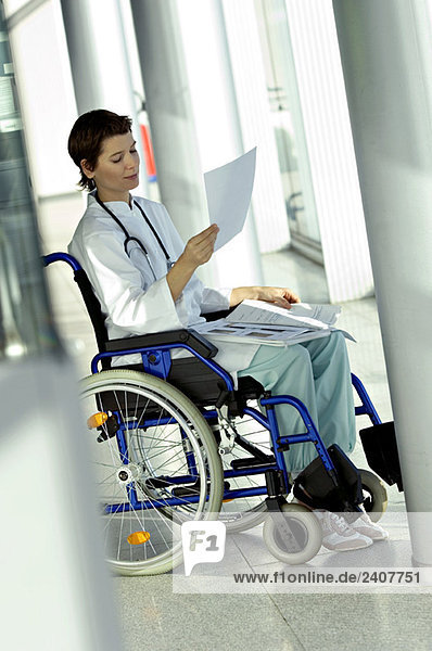 Ärztin sitzt im Rollstuhl und liest eine Krankenakte.